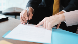 Woman pointing at contract for man to sign