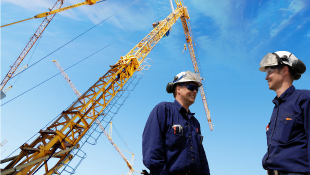 Two construction workers in front of mobile cranes