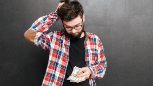 Confused man looking down at money worried