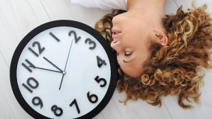 Woman lying down next to clock