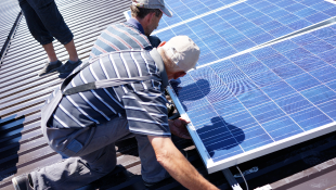 Two construction workers installing solar panels on roof