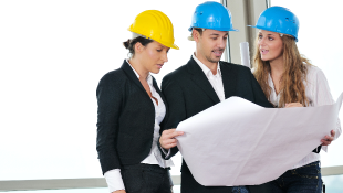 Business men and women in hardhats looking at blueprints