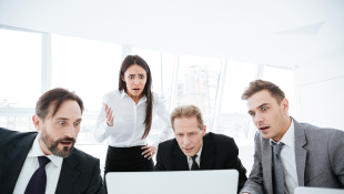 Business people staring at laptop screen with concern