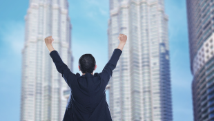 Business person standing with arms up in triumph