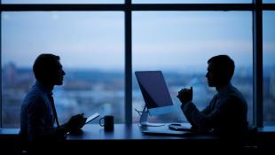 Businessmen meeting over computer in dark