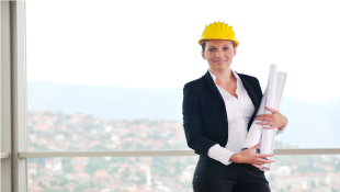 Female construction worker in hard hat and holding plans