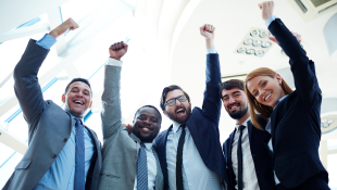 Business partners raising arms in triumph
