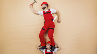 Construction worker standing on shoulders of another worker