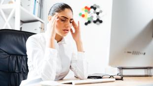 Businesswoman sitting at desk with headache