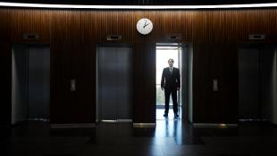 Businessman standing in darkened room