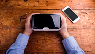 Desk with person holding VR equipment and cell phone