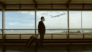 Man pulling luggage in airport terminal with jet taking through window.