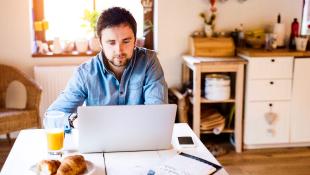 Businessman sitting over computer in kitchen
