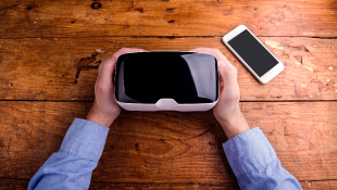 Man holding VR glasses on table with smartphone on table also