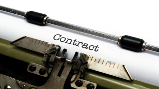 Word contract on paper in typewriter