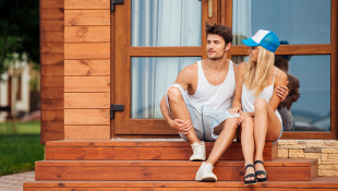 Young couple sitting in front of wooden house