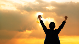 Businessman standing in front of sunset holding arms up in triumph