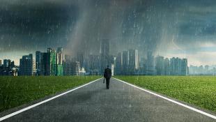 Businessman walking through storm toward city
