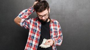 Confused man looking down at money worried