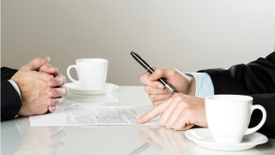 Businessmen sitting at table with cups over contract