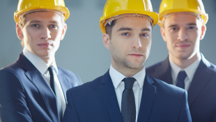 Three men in suits wearing construction hats