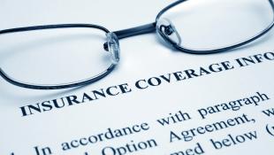 Glasses lying on Insurance Coverage document