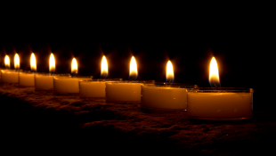 A line of lit candles in the dark