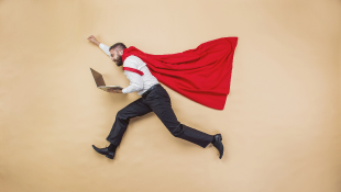 Businessman in super hero pose wearing cape