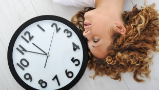 Woman lying next to clock