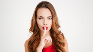 Woman holding finger over her mouth in silent gesture