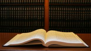 Law book open on desk in front of bookshelf