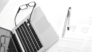 Laptop next to agreement with pen and glasses