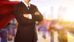 Businessman in suit and red cape in superman pose