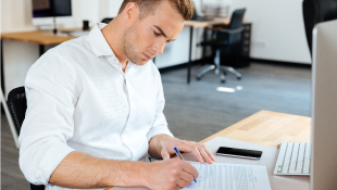 Businessman at desk signing contract