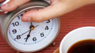 Person pressing alarm clock