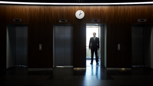 Businessman in doorway of elevator darkened room