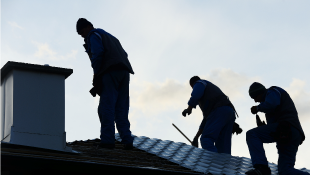 Three construction workers repairing roof