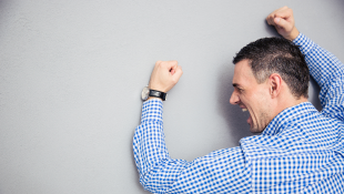 Businessman banging fists against wall