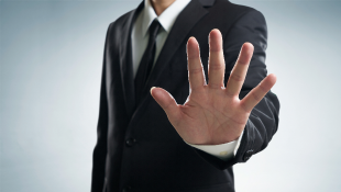 Businessman holding up a hand in a stopping gesture