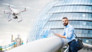 Drone hovering in front of building and man standing at rail