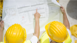 Two construction workers discussing blueprints