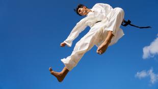 Martial artist kicking in air