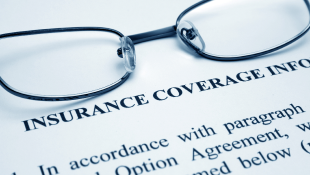 Glasses lying on Insurance Coverage document