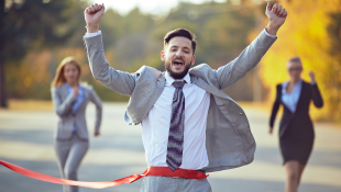 Man in suit running across finish line