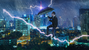 Businessman with umbrella battling thunderstorm with highrises behind him