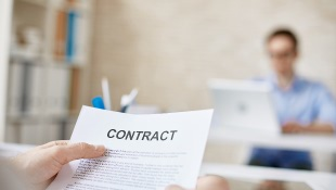 Hand holding contract with person in front of computer in background