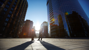 Two businessmen shaking hands in front of high rises