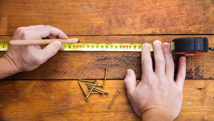 Hands holding a tape measure over a wooden table